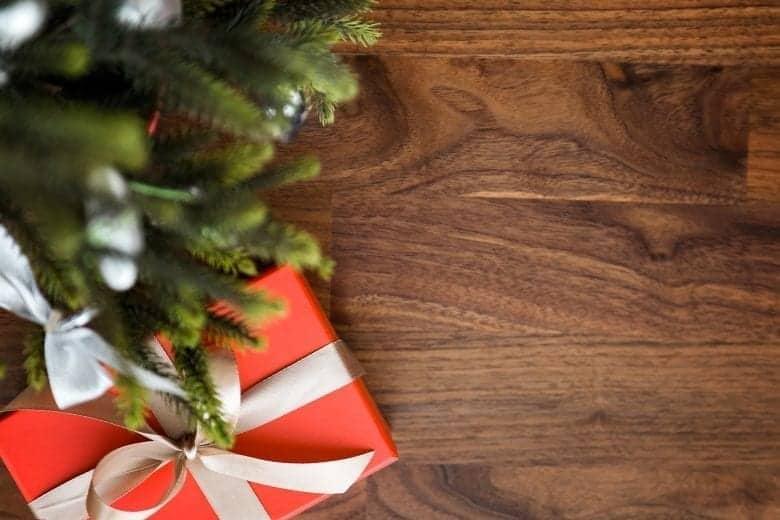 Χριστουγεννιάτικο Δώρο σε Ξύλινη Επιφάνεια πλάι στο Δέντρο